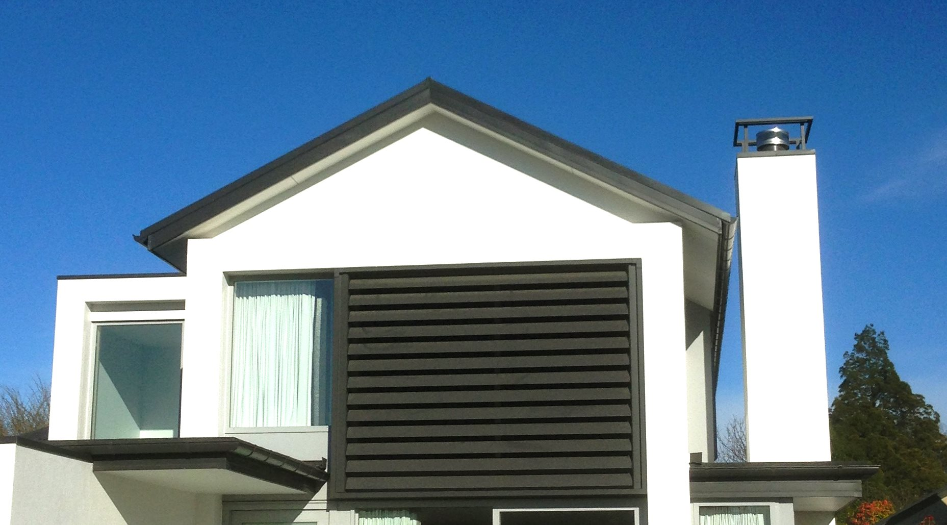 Closed Vertical louver covering window on the side of a house