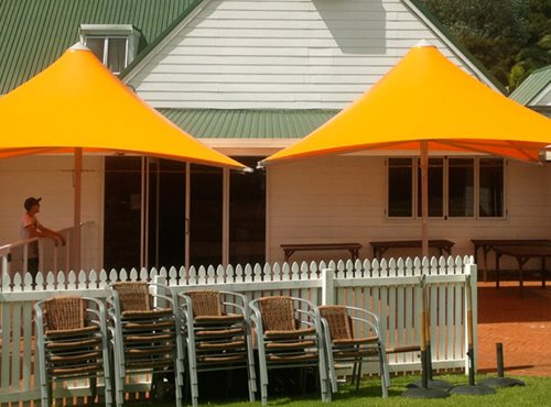Orange Parasol Umbrella's shading an outside area in front of a building