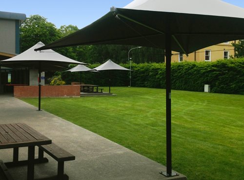 Parasol Umbrella placed around the rim of an outside dining area next to a grass field