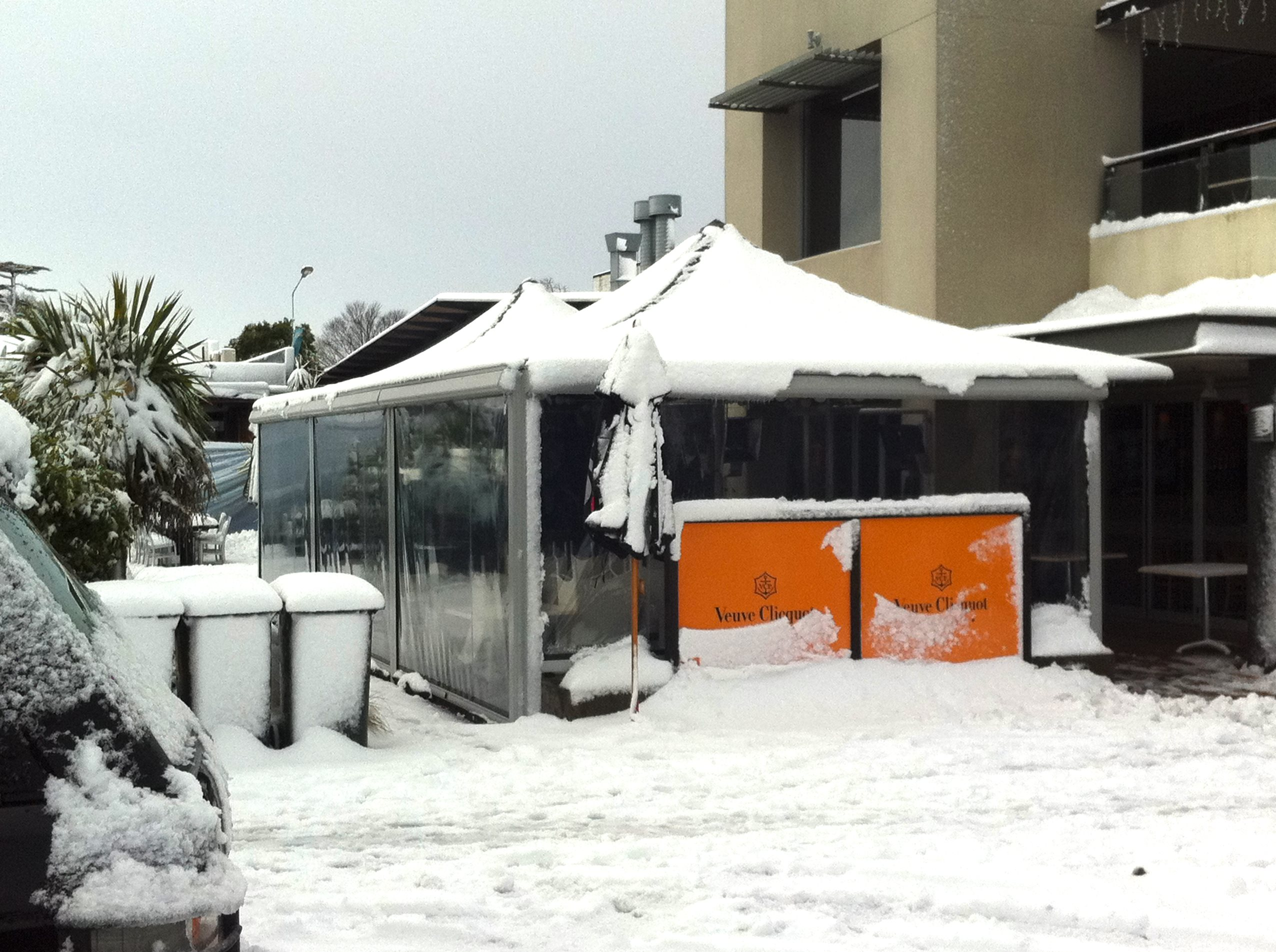 Parasol Umbrella withstanding the weight of a recent snow fall at a restaurant