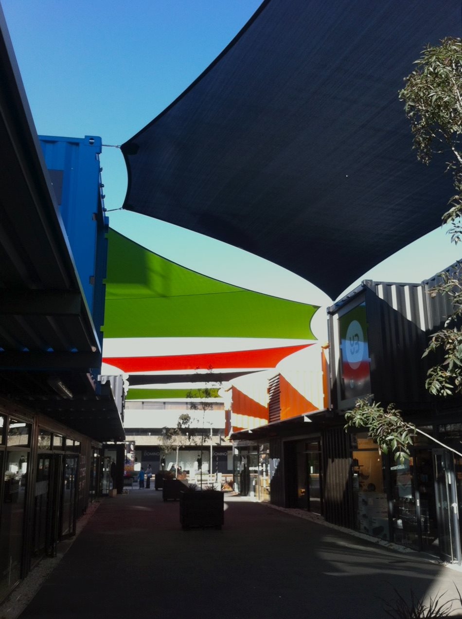 Large Shade Sails hanging over a public area surrounded by shops