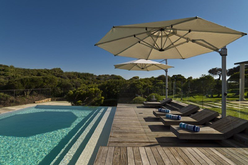 Cantilever Umbrella provding shade for lounging areas beside a pool
