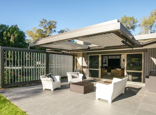 Outdoor heaters hanging on louver structure over outdoor sitting area
