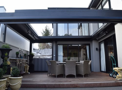 Outdoor heaters hanging on louver structure on outdoor porch